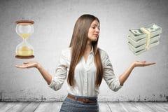Vidrio de la arena de la tenencia de la mujer de negocios y paquetes jovenes de dólares en sus manos en fondo gris de la pared imágenes de archivo libres de regalías