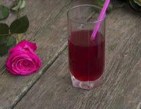 Vidrio de la bebida roja con un túbulo próximo una rosa Foto de archivo