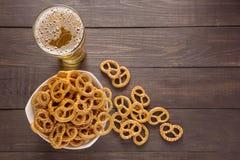 Vidrio de la cerveza y del pretzel en el fondo de madera Imágenes de archivo libres de regalías