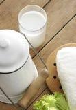 Vidrio de la leche fresca y de la leche-mantequera vieja Fotografía de archivo libre de regalías