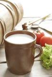 Vidrio de la leche fresca y de la leche-mantequera vieja foto de archivo libre de regalías