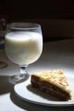 Vidrio de la leche y de un pedazo de torta Fotografía de archivo