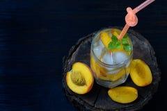 Vidrio de la limonada del melocotón o del cóctel hecha en casa fría del mojito con la menta en fondo oscuro Bebida de la soda Cop Imágenes de archivo libres de regalías