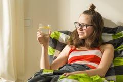 Vidrio de la mañana de agua con el limón en las manos del adolescente Forma de vida sana, dieta, antioxidante Fotos de archivo