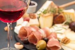 Vidrio de la placa del vino rojo y de queso de la falta de definición con queso mohoso de los pedazos Fotos de archivo