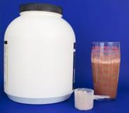 Vidrio de la sacudida de la proteína, cucharada, y envase grande Foto de archivo libre de regalías