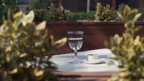 Vidrio de la taza de café del anuncio del agua en la tabla en el café lujoso de la terraza del verano almacen de video
