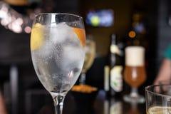 Vidrio de la vodka con el limón y rebanada anaranjada en barra del cóctel fotografía de archivo