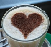 Vidrio de latte del café con el corazón del canela fotografía de archivo libre de regalías