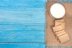 Vidrio de leche con los biscotes curruscantes del grano en un fondo de madera azul con el espacio de la copia para su texto Visió Imágenes de archivo libres de regalías