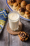 Vidrio de leche con los rollos de canela Foto de archivo libre de regalías