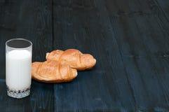 Vidrio de leche con pares de cruasanes en un viejo fondo de madera rústico con el espacio de la copia para su texto Visión superi Imagen de archivo libre de regalías
