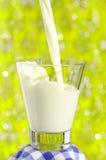 Vidrio de leche en fondo Fotos de archivo