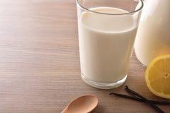 Vidrio de leche en los limones de la tabla y el primer de madera del canela Fotos de archivo