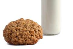 Vidrio de leche y de galletas aisladas en blanco Fotografía de archivo
