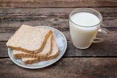 Vidrio de leche y de pan cortado en fondo de madera Imagen de archivo