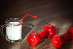 Vidrio de leche y de pesas de gimnasia Fotos de archivo libres de regalías