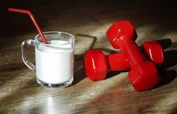 Vidrio de leche y de pesas de gimnasia rojas Imagenes de archivo