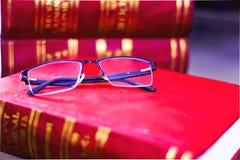VIDRIO DE LECTURA EN LOS LIBROS DE LEY EN UNA BIBLIOTECA imagenes de archivo