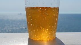 Vidrio de limonada contra la perspectiva del mar y del horizonte almacen de metraje de vídeo