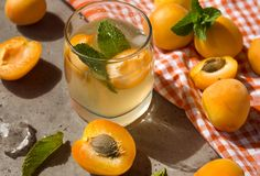 Vidrio de limonada del albaricoque, albaricoques frescos, rebanadas del albaricoque, menta, toalla fotografía de archivo