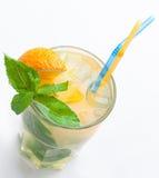 Vidrio de limonada fresca con la naranja, cubos de hielo, menta, paja Foto de archivo libre de regalías
