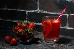 Vidrio de limonada de la cal de la fresa en un fondo de madera oscuro Foto de archivo libre de regalías