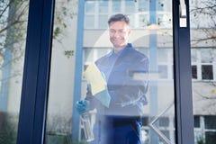 Vidrio de limpieza del trabajador de sexo masculino maduro feliz con el trapo Imagen de archivo