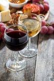 Vidrio de los vinos blancos y rojos, aperitivos en un fondo de madera Fotografía de archivo libre de regalías