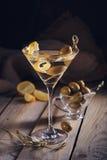 Vidrio de martini con las aceitunas verdes en una tabla de madera vieja imagen de archivo libre de regalías