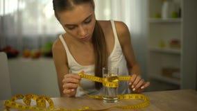Vidrio de medición anoréxico de la muchacha de agua con la cinta, cuerpo agotado, obsesión almacen de metraje de vídeo