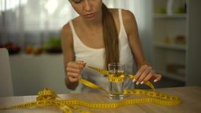 Vidrio de medición de la muchacha de agua con la cinta, cuerpo muerto de hambre, agotamiento, anorexia metrajes