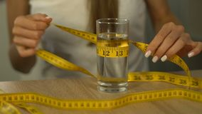 Vidrio de medición de la mujer de agua con la cinta-línea, obsesionado sobre calorías, anorexia almacen de video
