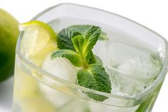 Vidrio de Mojito con las hojas de menta, la cal cortada y el primer del hielo en el fondo blanco Foto de archivo