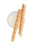 Vidrio de palillos de la leche y del wafel aislados sobre el fondo blanco Imagen de archivo