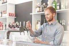 Vidrio de relleno del camarero joven del golpecito de la cerveza en el restaurante fotos de archivo libres de regalías