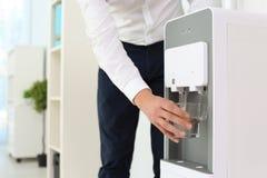 Vidrio de relleno del hombre del refrigerador de agua en la oficina, primer imágenes de archivo libres de regalías