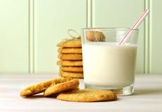 Vidrio de restauración de leche con una paja de beber, y bocado delicioso de las galletas de mantequilla hechas en casa de cacahu fotos de archivo