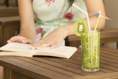 Vidrio de smoothie del kiwi y de una lectura del libro Fotografía de archivo libre de regalías