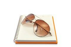 Vidrio de Sun colocado en el cuaderno Imagen de archivo
