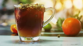 Vidrio de té de hielo con los hrysanthemums del  de Ñ y anaranjado, cubos de hielo en la tabla de madera oscura