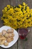 Vidrio de té, ramo de flores amarillas y placa con las galletas Fotografía de archivo libre de regalías