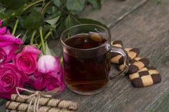 Vidrio de té y de galletas en una placa con un ramo de rosas Fotos de archivo libres de regalías