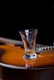 Vidrio de tequila en la guitarra eléctrica Foto de archivo libre de regalías