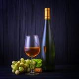 Vidrio de vino blanco con una botella y las uvas fotos de archivo