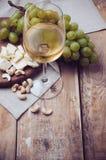 Vidrio de vino blanco, de las uvas, de los anacardos y de queso suave imágenes de archivo libres de regalías