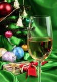 Vidrio de vino blanco en un fondo hermoso de la Navidad Foto de archivo libre de regalías