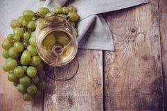 Vidrio de vino blanco y de las uvas foto de archivo