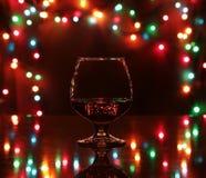 Vidrio de vino chispeante del shampagne del coñac o del brandy en fondo del oro Fotos de archivo libres de regalías