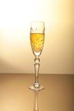Vidrio de vino chispeante del shampagne en fondo del oro Imagen de archivo